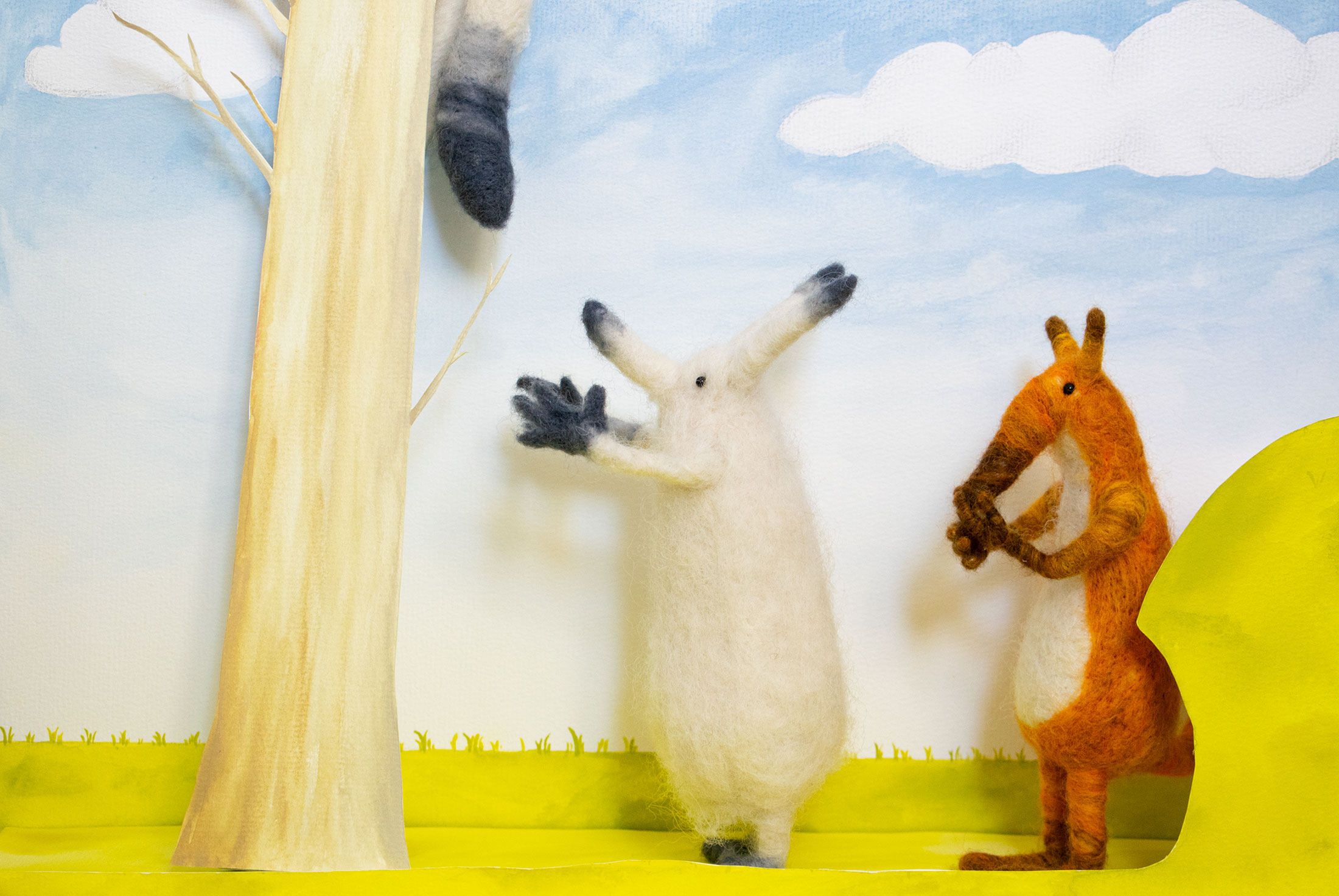A white and grey needle felted foxes, and a white, orange and brown felted fox, face the left of the screen, looking at a tree upon whose branch the white fox's tail is hanging down.
