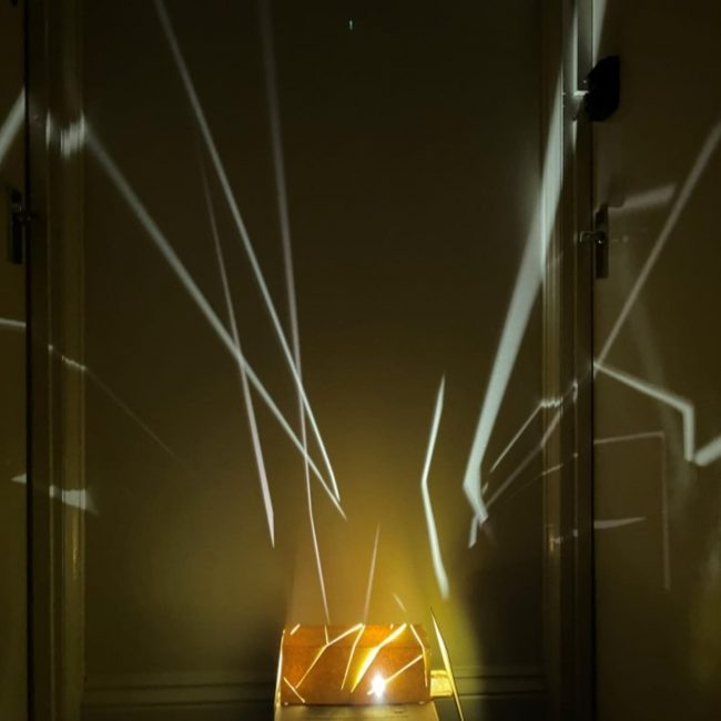 A light fixture prototype made out of paper that creates line patterns when lit up.